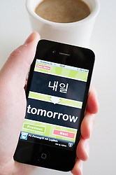 Student learning Korean language using an education app on an iPhone 4g smart phone
