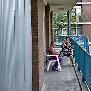 Nederland Rotterdam 04-07-2009 20090704 Foto: David Rozing ..Achterstandswijk Pendrecht Rotterdam zuid, leegstaand pand afgesloten met stalen platen, allochtone vrouwen drinken een biertje op de gallerij. deprived area / projects pendrecht this area is on a list with projects which need help of the government because of degradation in the area etc., project, suburb, suburbian, problem. Neighboorhood, neighboorhoods, district, city, problems,  daily life Holland, The Netherlands, dutch, Pays Bas, Europe  Holland, The Netherlands, dutch, Pays Bas, Europe, leeg, leegstand, onbewoond, onbewoonde, woning, appartement, etagewoning, vastgoed, toezicht, politie, politiewagen, politietoezicht, moslima's, moslima, overzicht, general view, politieauto..Foto: David Rozing
