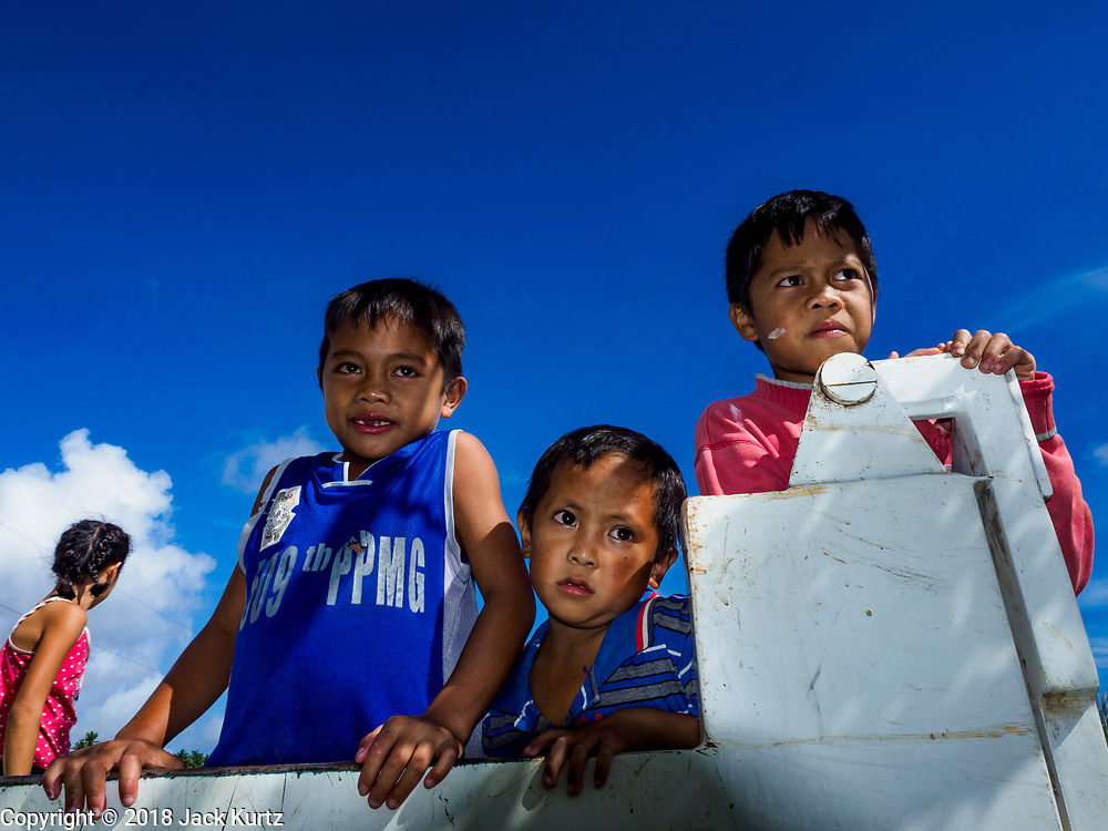 "22 JANUARY 2018 - CAMALIG, ALBAY, PHILIPPINES:  Boys in a government truck wait to be taken to an evacuation center. Their family had to leave their home on the slope of the Mayon volcano. There were a series of eruptions on the Mayon volcano near Legazpi Monday. The eruptions started Sunday night and continued through the day. At about midday the volcano sent a plume of ash and smoke towering over Camalig, the largest municipality near the volcano. The Philippine Institute of Volcanology and Seismology (PHIVOLCS) extended the six kilometer danger zone to eight kilometers and raised the alert level from three to four. This is the first time the alert level has been at four since 2009. A level four alert means a ""Hazardous Eruption is Imminent"" and there is ""intense unrest"" in the volcano. The Mayon volcano is the most active volcano in the Philippines. Sunday and Monday's eruptions caused ash falls in several communities but there were no known injuries.   PHOTO BY JACK KURTZ"