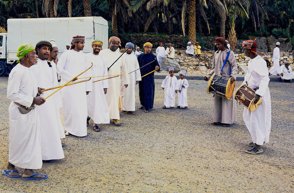 Oman, Wadi Bani Khalid.  Two drummers and a row of village men in traditional clothing dance and sing, waving canes,  before a wedding.
