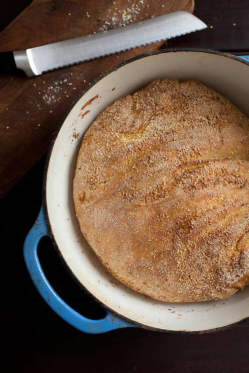 A round loaf of bread baked in a blue and white dutch oven with a serrated bread knife next to it.