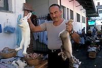 Merchant holding two rabbits for sale for food in a market in Ischia, an island near Naples - Photograph by Owen Franken
