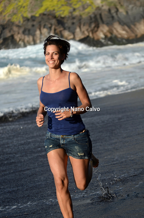 Young attractive woman running on the beach