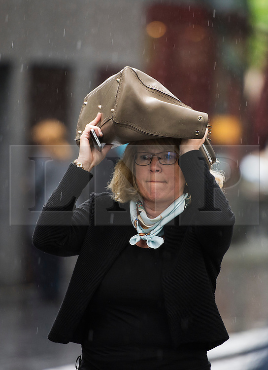 © Licensed to London News Pictures. 29/05/2015. London, UK. A woman using her handbag to shelter from the rain near Tower Bridge in central London on a wet and rainy morning.. Photo credit: Ben Cawthra/LNP
