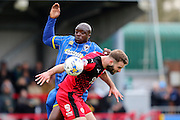 Bayo Akinfenwa forward for AFC Wimbledon (10) and Crawley Town Defender Joe McNerney (5) tussle during the Sky Bet League 2 match between AFC Wimbledon and Crawley Town at the Cherry Red Records Stadium, Kingston, England on 16 April 2016. Photo by Stuart Butcher.