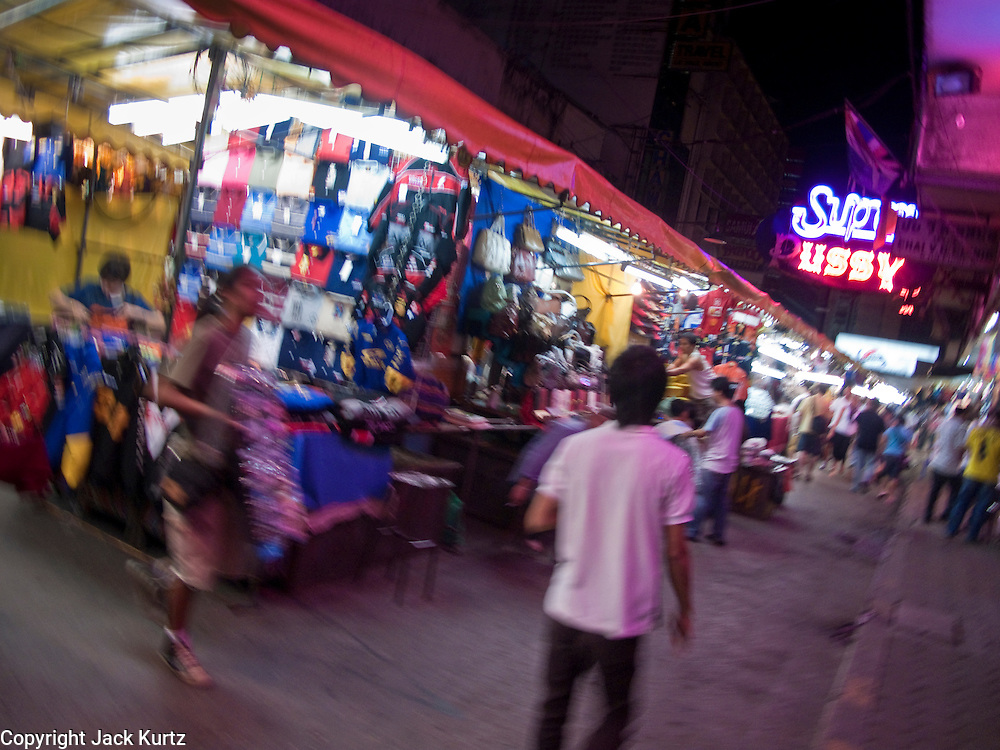 08 OCTOBER 2009 -- BANGKOK, THAILAND:  Merchants set up their market stalls in the Patpong night market along Patpong Sois 1 and 2. The night market is a major tourist shopping area in Bangkok. The Patpong area used to be famous as an adult entrainment district but now its night market is equally famous.   PHOTO BY JACK KURTZ