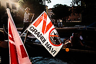 Un gondoliere in Rio di San Trovaso lavora mentre nel vicino canale della Giudecca si sta svolgendo una manifestazione contro le grandi navi. 25 settembre 2016.