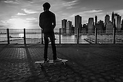 A teenager rides a skateboard on the brooklyn Eights Promenade with the Manhattan skyline in the background. Brooklyn Eights, New York, 2010.