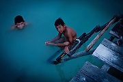 Two young boys swim at dusk in Lake Petén Itzá near the village of El Remate, located in the Petén region of Guatemala.