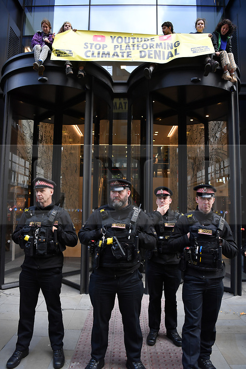 © Licensed to London News Pictures. 16/10/2019. London, UK. City of London police hold the line as Young Extinction Rebellion activists (XR Youth) block the entrance to Google owned Youtube in Kings Cross London, calling for accurate representation on climate change on their platform. Photo credit: Guilhem Baker/LNP