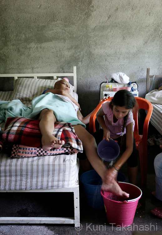 Mariana de la Torre, 29, gets her feet washed by her daughter Andrea, 11, on her bed at her house in Apatzingan, Mexico on March 19, 2009.<br /> (Photo by Kuni Takahashi)