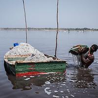 Un homme charge sa barque de sel avec son tamis.