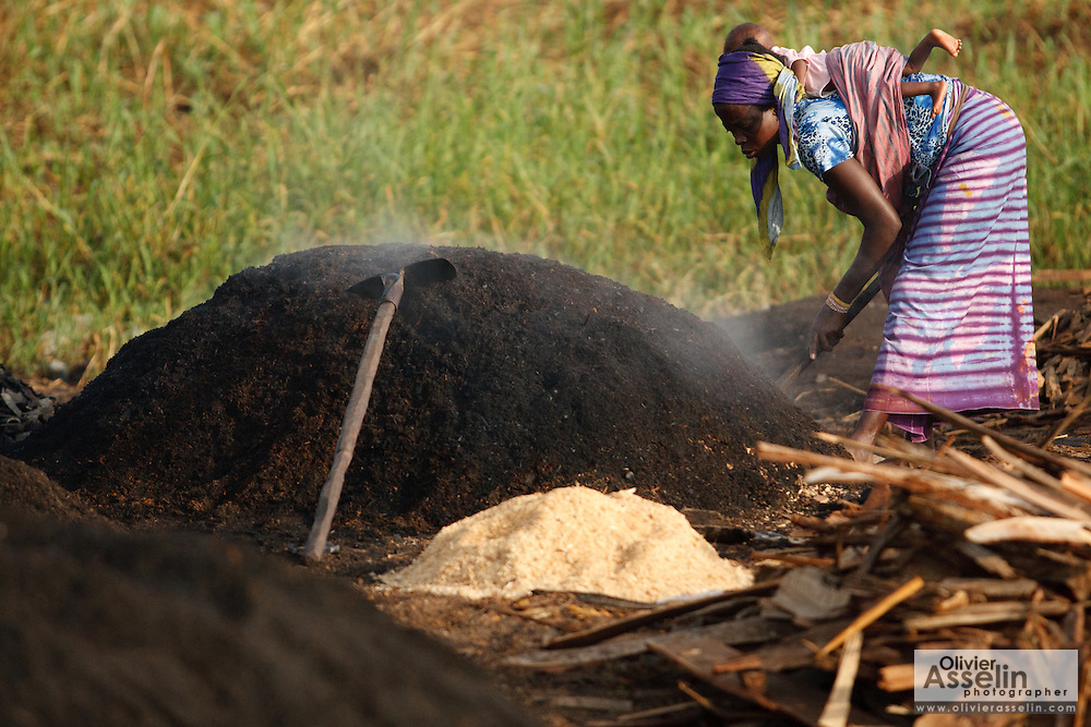 A woman carrying an infant on her back works at a wood charcoal production site on the outskirts of San Pedro, Bas-Sassandra region, Côte d'Ivoire on Sunday March 4, 2012. Men, women and children - who don't go to school - work here seven days a week.