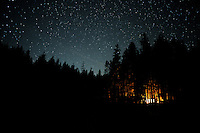 Campfires glow under a stunning night sky, along the banks of the Metolius River<br /> <br /> Shot in Oregon, USA