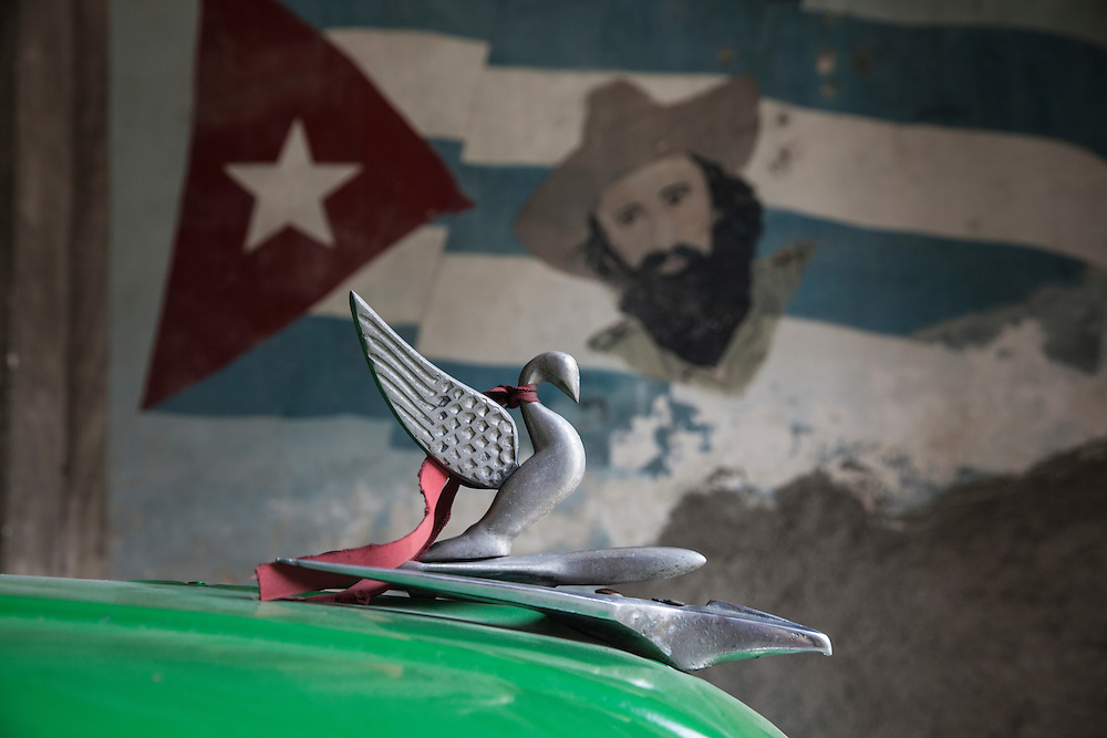 An automotive brand emblem stands out from a  painting of the Cuban flag and Fidel Castro on a wall in the background.<br />