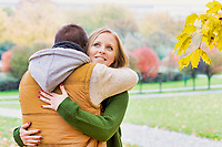 Portrait of man embracing his beautiful wife in park