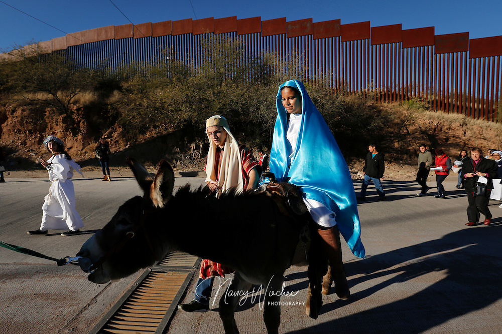 "Catholic high school students Saul Gonzalez and Kenia Salas play the parts of Joseph and Mary as they make their way along the international border fence in Nogales, Sonora, Dec. 20. Kino Teens from Salpointe and Lourdes Catholic high schools in Nogales, Arizona, led the bi-national ""posada"" recalling Mary and Joseph's search for shelter before the birth of Christ. The annual event held by  the Kino Border Initiative and Dioceses Without Borders reflected on the struggles of migrants and migrant families. (CNS photo/Nancy Wiechec)"