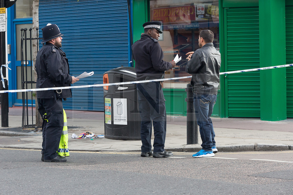 © Licensed to London News Pictures. 27/09/2015. London, UK. Police officers speaking to a local resident at the police cordon on Chatsworth Road. Police have launched a murder investigation after a man was shot dead in the street outside Regal Pharmacy next to Mighty Meats butcher shop in Chatsworth Road, Hackney, east London yesterday. Photo credit : Vickie Flores/LNP