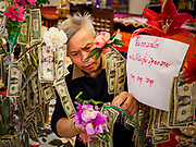 14 APRIL 2019 - DES MOINES, IOWA: A man puts dollar bills on a money tree which will be donated to the temple during Lao New Year, also called Songkran,  observances at Wat Lao Buddhavath in Des Moines. Several thousand Lao people live in Des Moines. Most came to the US after the wars in Southeast Asia. Songkran is celebrated in Theravada Buddhist countries (Sri Lanka, Myanmar, Thailand, Laos, and Cambodia) and in Theravada Buddhist communities around the world.      PHOTO BY JACK KURTZ