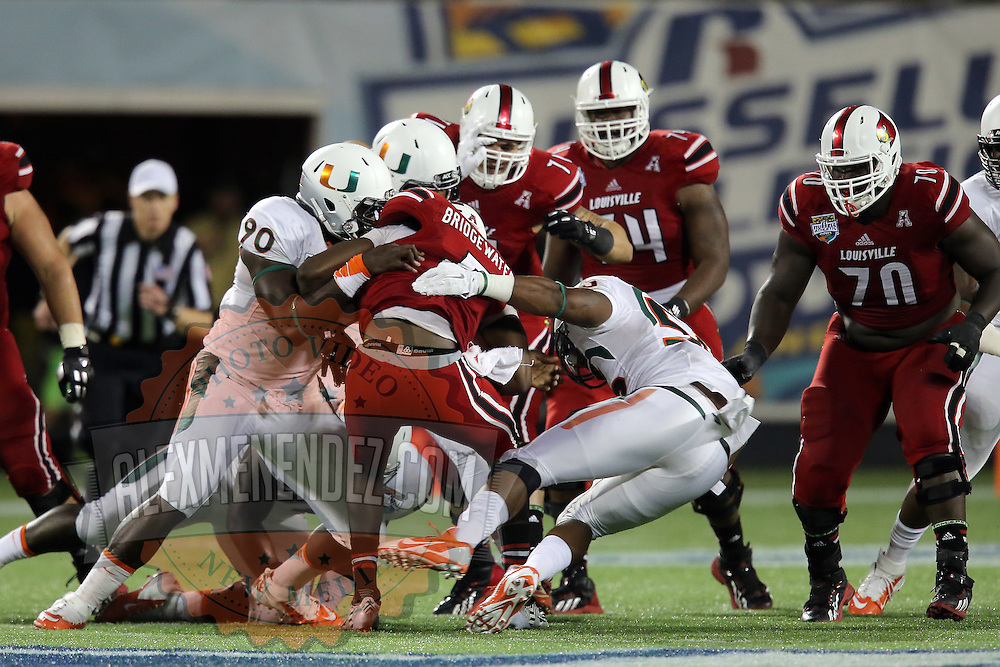 Louisville Cardinals quarterback Teddy Bridgewater (5) gets wrapped up by the defense during the NCAA Football Russell Athletic Bowl football game between the Louisville Cardinals and the Miami Hurricanes, at the Florida Citrus Bowl on Saturday, December 28, 2013 in Orlando, Florida. Louisville won the game by a score of 36-9. (AP Photo/Alex Menendez)