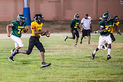 Raekoi Evans runs the ball.  Avengerz vs. Sharks .  Lionel Roberts Stadium.  St. Thomas, VI.  15 August 2015.  © Aisha-Zakiya Boyd