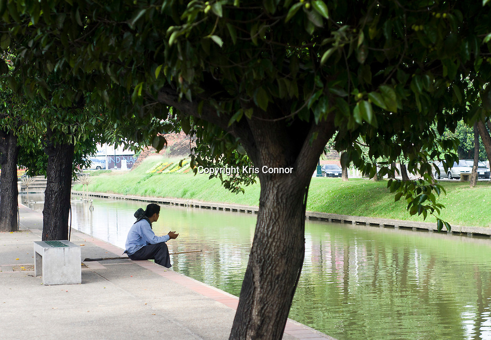 A man sits along the moat along the old city in Chiang Mai, Thailand. Photo by Kris Connor