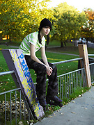A young woman sat on a railing wearing rollerblades.