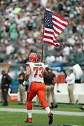 Cleveland Browns tackle Joe Thomas (73) runs onto the field carrying a large American flag during pregame festivities held on honor of the lives lost in the 911 terror attacks on the United States prior to the 2016 NFL week 1 regular season football game against the Philadelphia Eagles on Sunday, Sept. 11, 2016 in Philadelphia. The Eagles won the game 29-10. (©Paul Anthony Spinelli)