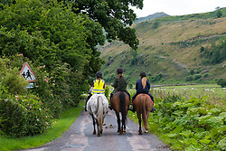 Three female horse riders riding horses in lane in middle of Argyll and Bute in Scotland United Kingdom
