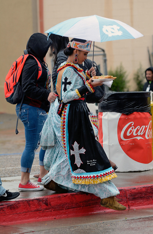 jt042817p/a sec/jim thompson/  Mikayla Hunt holds up the dress of her cousin Kaloni Walton of North Carolina to keep it out of the water as they return to Tingley Coliseum for  2017 Gathering of Nations Pow-Pow.  Friday April 28, 2017. (Jim Thompson/Albuquerque Journal)