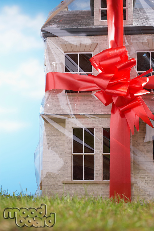Model house gift-wrapped with red ribbon and bow close-up