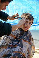 A Syrian boy gets a haircut in Atmeh refugee camp, home to approximately 11,000 people displaced in Syria's civil war.