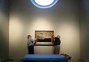 Brothers Sean (left) and Dennis Tarpey of Northern Artery Art Movers hang a painting depicting the summit of Mount Washington as employees, volunteers and contractors hang the first exhibit at the Museum of the White Mountains in Plymouth, New Hampshire.