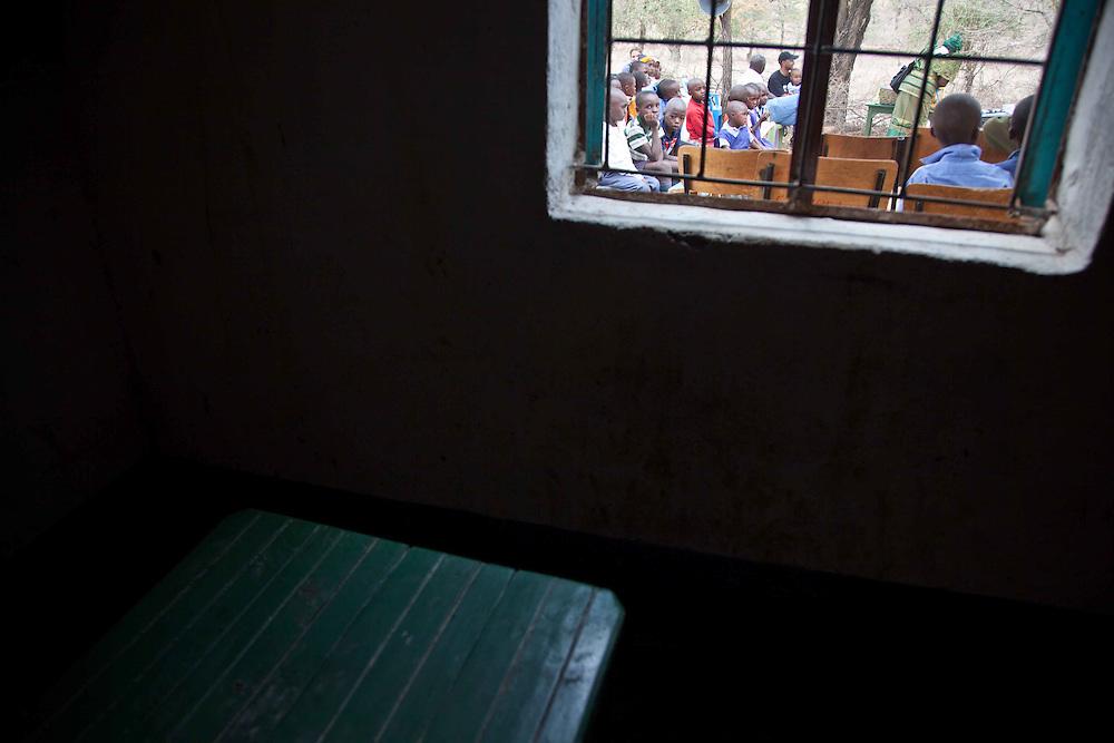 Children are photographed from the inside of a library in a rural community of Makueni County, Kenya.
