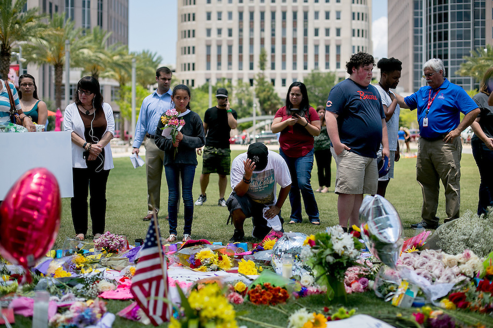 ORLANDO - JUNE 14, 2016: Mourners gather at a memorial outside the Dr. P. Phillips Center for the Performing Arts in memory of the victims of the Pulse nightclub in Orlando, Florida. CREDIT: Sam Hodgson for The New York Times.