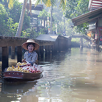 A woman rowing her boat at Damnoen Saduak canal.