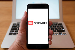 Using iPhone smartphone to display logo of DB Schenker; logistics division of DB, Deutsche Bahn.