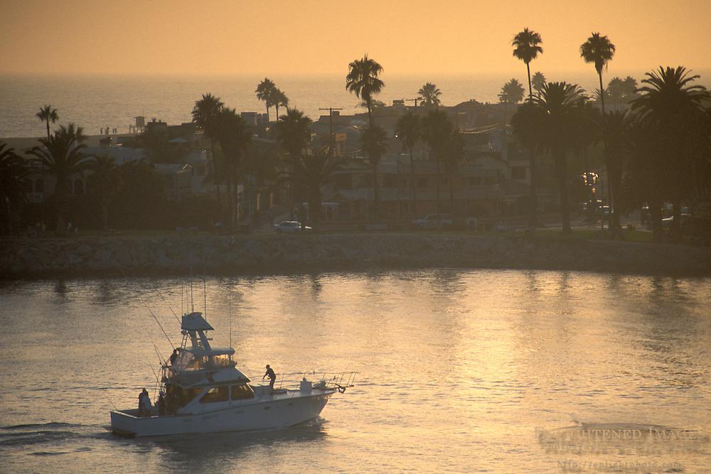 Luxury yacht returning to harbor port at sunset, Newport Beach, Orange County, California