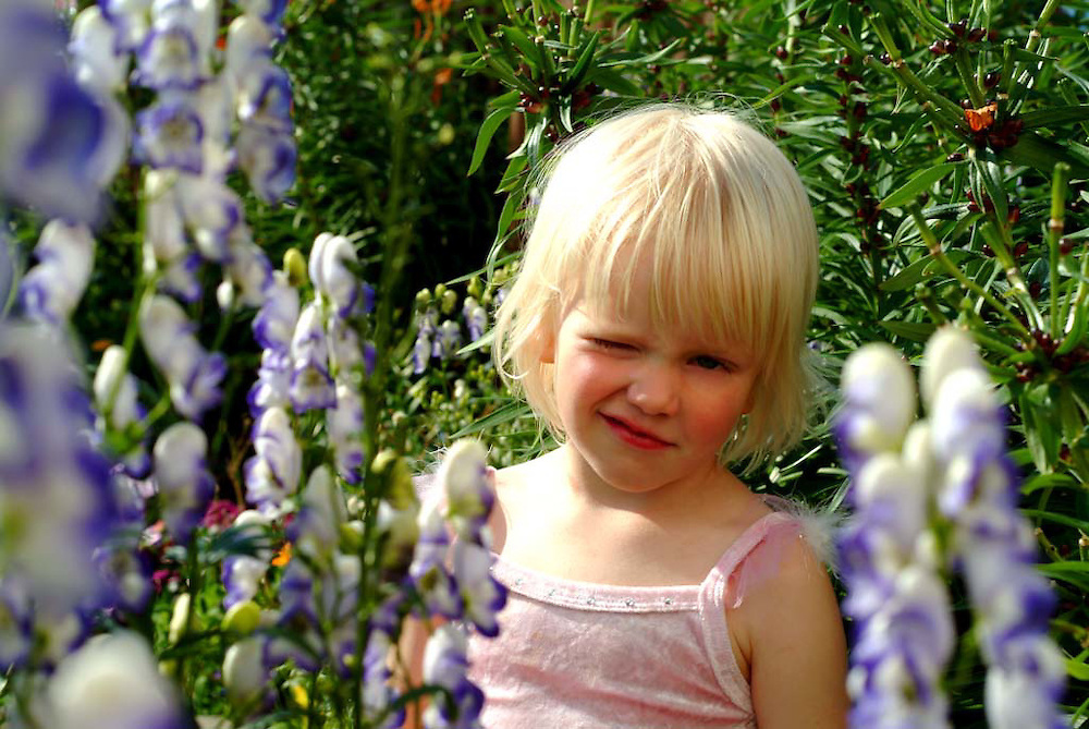 A girl smiles at the camera surrounded by trees and flowers.