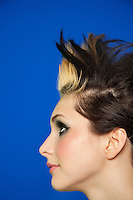 Side view of young woman with spiked hair over colored background