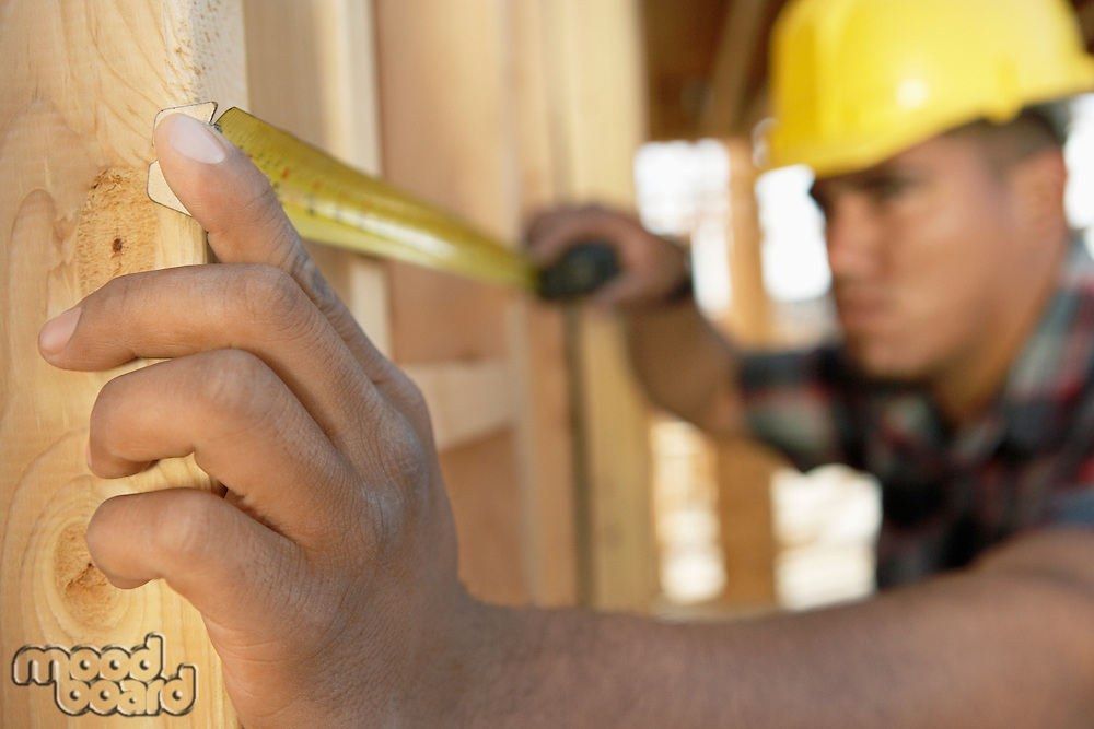 Construction Worker measuring between boards with tape measure on construction Site