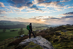 © Licensed to London News Pictures. 31/03/2016. Baildon UK. Picture shows a walker taking a break to watch this morning's sunrise on Baildon Moor in Yorkshire. Photo credit: Andrew McCaren/LNP