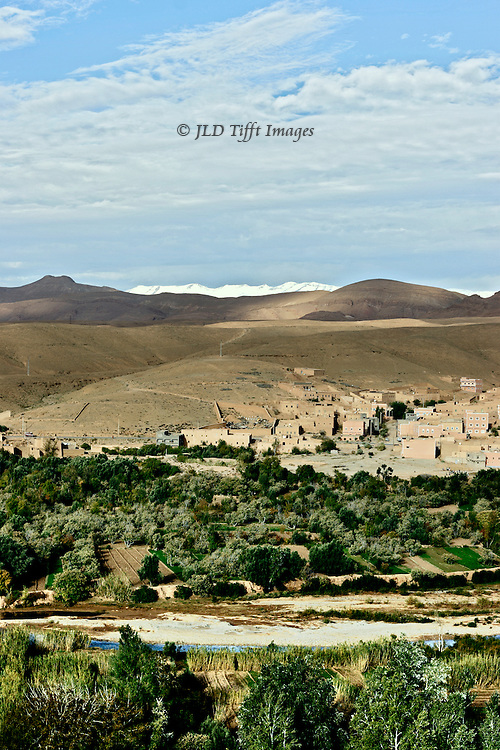 General view showing, in the foreground, agricultural land of planted fields, orchards, palm trees; then a river low in water; in the middle distance, a mud brick village, with mosque minaret; in the distance, bare hills rising toward the Atlas Mountains.  In the far distance, snow-capped peaks.
