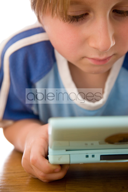Boy Playing with Handheld Video Game