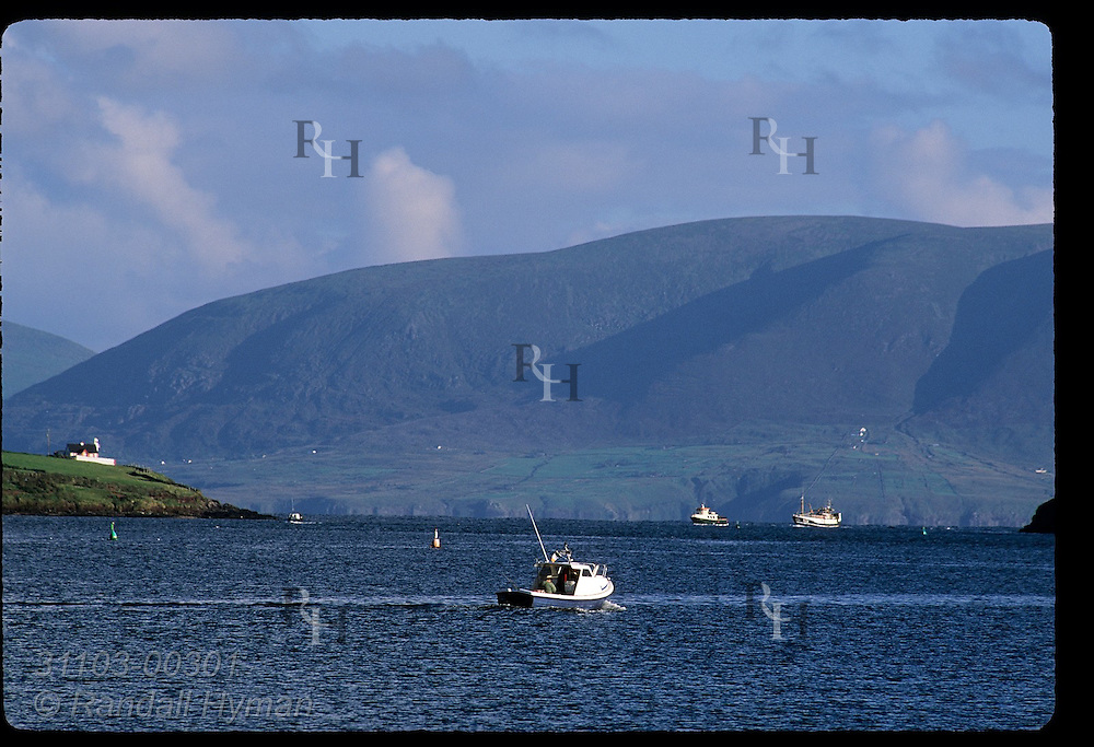 Small fishing boat cruises across Dingle Harbour toward Dingle Bay; Dingle, Ireland.