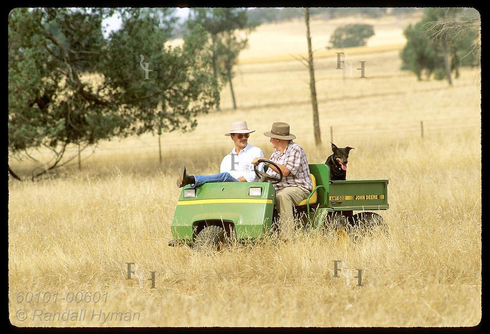 Farmer Jack Veitch sits in all-terrain vehicle talking with Zel Bodulovic in field;Coolamon, NSW Australia