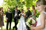 Young girl holding bouquet bride and groom in background side view