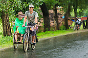 14 JUNE 2013 -  PANTANAW, AYEYARWADY, MYANMAR:  A woman gets a ride in a pedicab in the rain along Highway 5 in Pantanaw, Ayeyarwady, in the Irrawaddy delta region of Myanmar. This region of Myanmar was devastated by cyclone Nargis in 2008 but daily life has resumed and it is now a leading rice producing region.  PHOTO BY JACK KURTZ