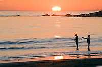 Silhouette of two fishermen with the sunset over the ocean at Refugio State Park in Gaviota, California.