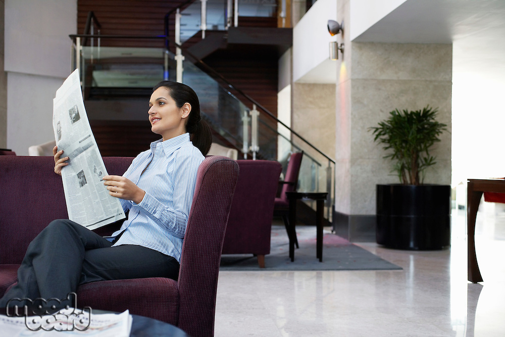Business woman reading newspaper in hotel lobby